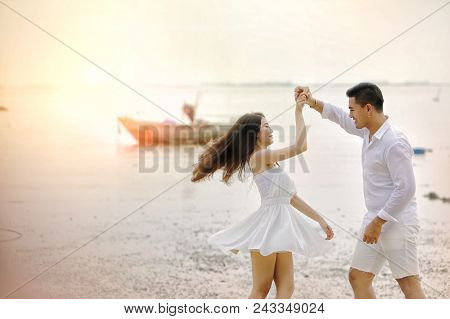 Valentines Day, Couple In Love. Couple On The Beach. Smiling Couple Holding Hands On The Beach. Asia