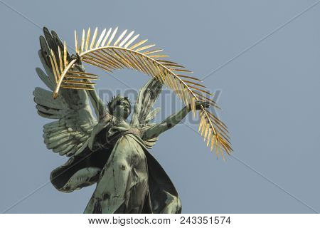 Bronze Sculpture Genius With Palm Branch And Wings On The Roof Of The Opera House In Lvov. Blue Sky