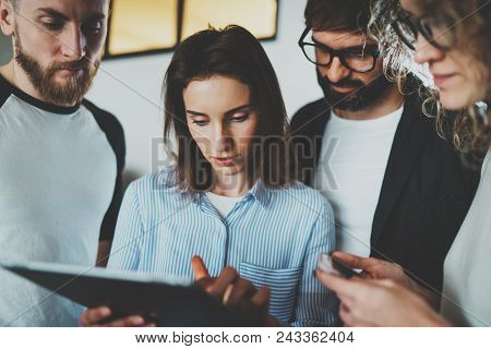Working Moments Photo.group Of Young Coworkers Using Electronic Touch Pad Together At Modern Office