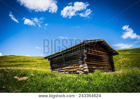 A Small Mountain Hut Surrounded By Grassland