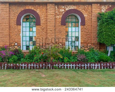 Orange Colored Bricks Stone Wall With Two Big Old Grunge Windows Covered With Green Metal Grid, Gree