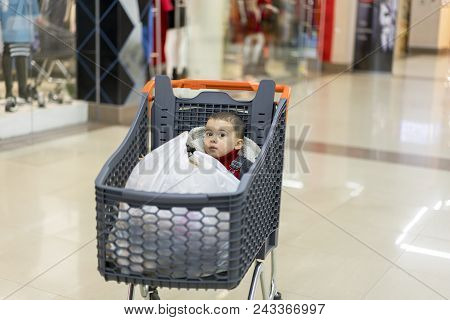 A Trolley With Products In Which The Child Sits. Full Cart With Food In The Supermarket. In The Cart