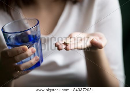 Female hands holding pill and glass of water, woman taking supplements or antibiotic antidepressant painkiller medication to relieve pain headache, contraception side effects concept, close up view poster