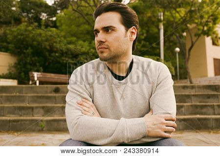 Portrait Of Pensive Cute Young Caucasian Hipster In Informal White Jersey Sitting At Sunny City Park