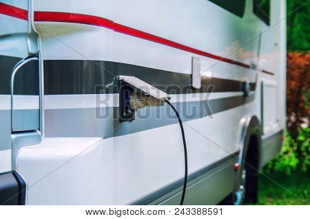 Motorhome Stillife. Concept Of Power Supply Of The Camper. Plug Of The Electric Wire Is Inserted Int