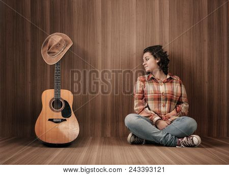 Teenager In A Wooden Rooml And Looks At A Guitar Covered With A Cowboy Hat