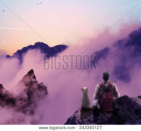 Young Man And His Cat On Top Of A Mountain Hill Admiring The View.