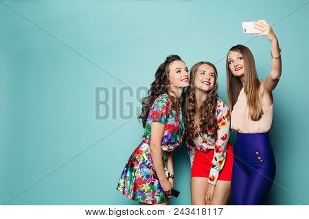Fashionable Women Wearing In Brigth Clothes Spending Time Together, Making Photo At Smart Phone.thre