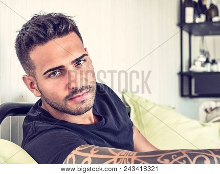 Handsome Green Eyed Young Man Relaxing At Home Sitting On His Couch, Looking At Camera