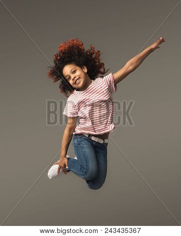 Beautiful Little African-american Girl Jumping A Gray Studio Background, Copy Space. Studio Shot Of