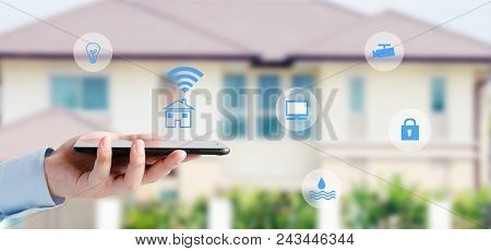 Hand Using Smart Phone As Smart Home Control Over Blur House Background, Smart Home Control Concept