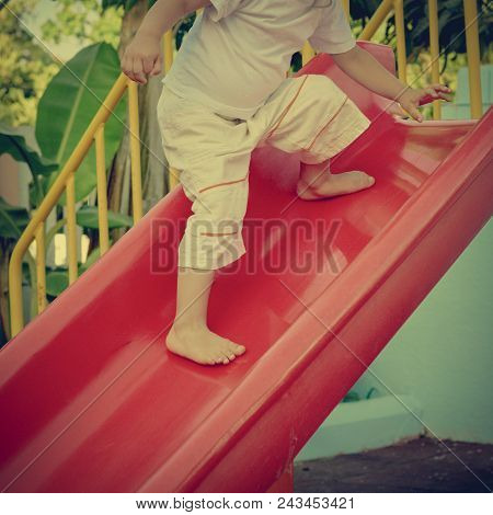 Part Of Boy Playing On Slide In Tropical Resort. Image With Warm Vintage Toning