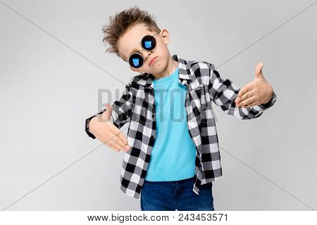 A Handsome Boy In A Plaid Shirt, Blue Shirt And Jeans Stands On A Gray Background. The Boy Is Wearin