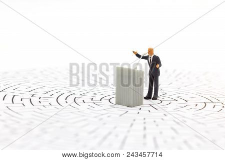 Miniature People: Businessman Stand With The Podium On Center Of Maze. Concepts Of Finding A Solutio