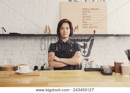 Smiling Barman Welcoming Guests At Coffee House Counter. Portrait Of Young Woman In Uniform At His W