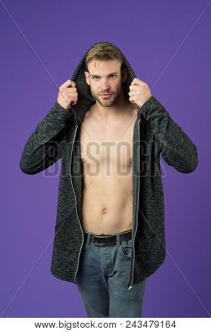 Man On Smiling Face Tries On Jacket With Hood, Violet Background. Guy With Bristle On Face And Smoot