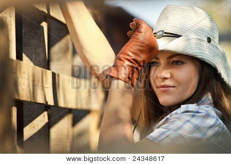 Retrato de hermosa vaquera en stetson junto a la valla de madera