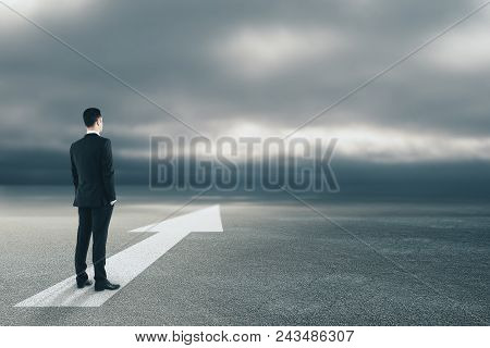Businessman Standing On Abstract Road With Arrow. Dull Sky Background. Success And Forward Concept