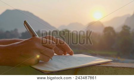 Young Woman Writing Travel Notes In Diary During Sunrise With Beautiful Sun Light And Mountain Lands