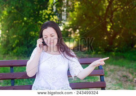 Young Beautiful European Girl Sitting On A Bench And Talking On The Phone. The Girl Points A Finger
