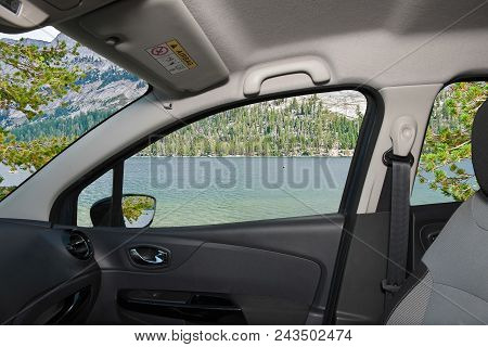 Looking Through A Car Window With View Of A Beautiful Green Valley And Lake In Yosemite National Par