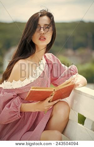 Sexy Woman. Woman With Brunette Hair In Sexy Dress Relaxing On Nature. Girl In Glasses Reading Book.