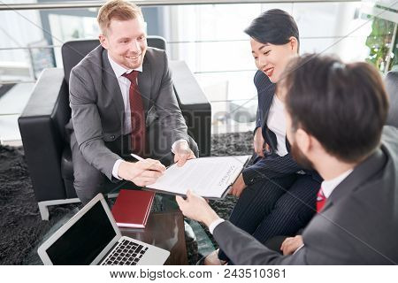 Cheerful Entrepreneur Wearing Elegant Suit Sitting On Cozy Armchair And Signing Contract After Succe