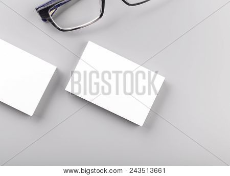 Photo Of White Business Cards Isolated On Gray Background With Glass. Template For Branding Identity