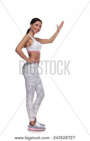 side view of fitness smiling woman presenting to side. She is standing on white background with hand on hip