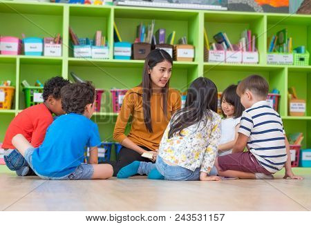 Asian Female Teacher Teaching Mixed Race Diversity Group Of Kids Reading Book Sitting On Library Flo