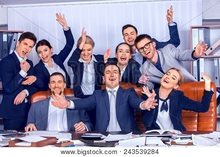 Business people office life of team people are happy with hand up sitting table. Cabinets with folders in background. People in suits glad with successful deal. Complex market conditions of our time.