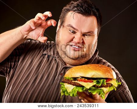 Diet failure of fat man eat fast food. Breakfast for mad overweight person who eating huge hamburger. Junk meal leads to obesity concept on black background. Feast for occasion. poster