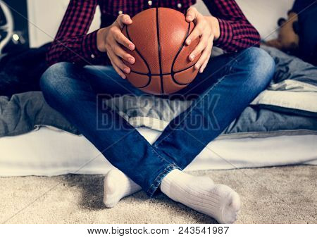 Teenage boy in a bedroom holding a basketball hobby aspiration and loneliness concept
