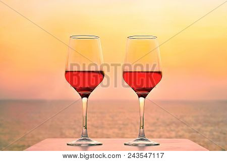 Two Glasses Of Red Wine On A Background Of Sea Horizon Evening. Two Glasses Of Red Wine At Sunset Se