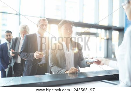 Young delegate in formalwear passing registration by check-in counter before departure