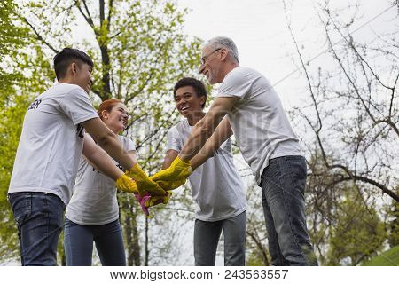 Team Spirit. Low Angle Of Optimistic Vigorous Volunteers Standing And Holding Hands Together