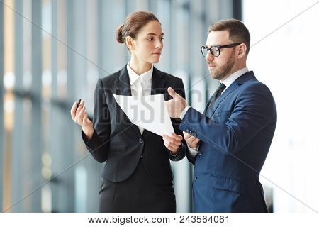 Serious businessman explaining some points in document while discussing paper with colleague