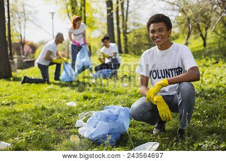 Volunteering Problem. Cheerful Male Volunteer Smiling To Camera While Collecting Litter