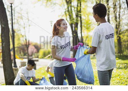 Volunteer For Country. Cheerful Two Volunteers Holding Garbage Bag And Staring At Each Other