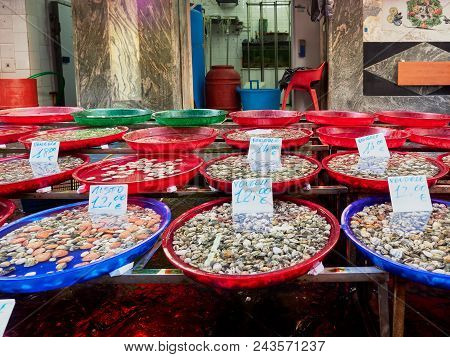 Plastic bowls with delectable fresh shellfish standing on stall in market in Napoli, Italy poster