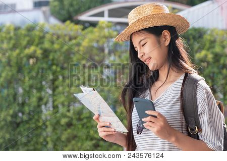Asian Woman Traveler Backpacker Use Map And Mobile Phone App To Search For Route Location Of Place W