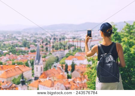 Woman Tourist Takes A Picture Panoramic View With Red Roofs Of Ljubljana From Castle On Smart Phone.