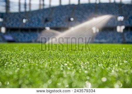 Grass On Stadium In Sunlight. Closeup Of A Green Football Field. Wet Stadium Grass In The Morning Li
