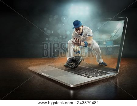 Caucassian baseball Player in dynamic action with ball in a professional sport game play on the laptop in baseball under stadium lights.