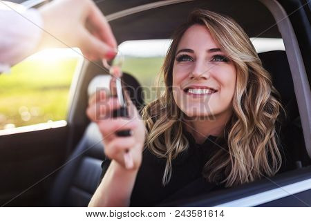 An Attractive Woman In A Car Gets The Car Keys. Rent Or Purchase Of Auto - Concept.