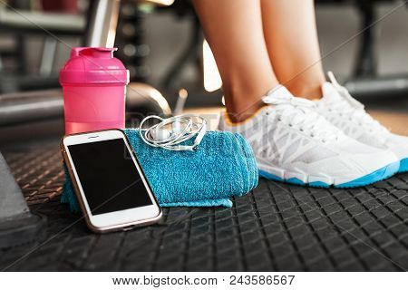 Pink Shaker, Blue Towel, White Smartphone And Earphones On The Black Rubber Floor Above Fitness Woma