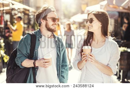 Couple Of Stylish Young Casual Teens With Sunglasses Holding Cups Of Coffee Walking Down The Street