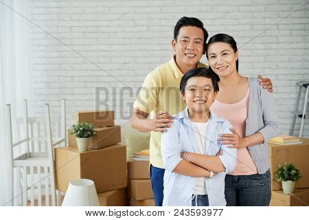 Group Portrait Of Happy Asian Family Of Three Looking At Camera With Wide Smiles While Distracted Fr