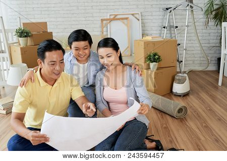 Cheerful Asian Family Of Three Gathered Together At Spacious Living Room Of New Apartment And Studyi