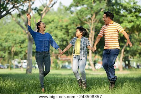 Joyful Asian Family Of Three Holding Hands And Jumping In Air While Spending Warm Summer Day At Gree